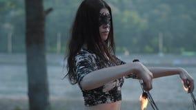 Portrait de femme mignonne de grâce dans le masque exécutant une exposition avec la position de flamme sur la rive devant des arb clips vidéos