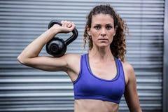 Portrait de femme musculaire s'exerçant avec le kettlebell Photographie stock