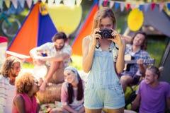 Portrait de femme prenant une photo des amis au terrain de camping Photographie stock