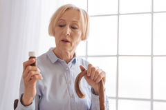 Portrait de femme sérieuse cette bouteille de regard avec la médecine Image stock