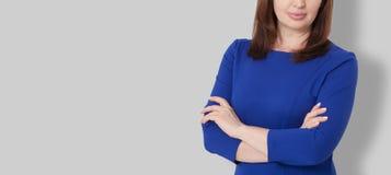 Portrait de femme sérieuse de patron de Moyen Âge de brune dans la robe d'affaires d'isolement sur le fond gris Bras croisés sur  photographie stock libre de droits