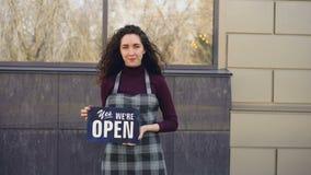 Portrait de femme sûre attirante dans le petit entrepreneur de tablier tenant le ` oui nous sommes extérieurs debout de signe ouv