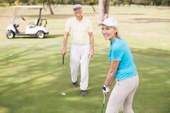 Portrait de femme sûre de golfeur par l'homme Image libre de droits