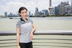Portrait de femme se penchant sur la balustrade par la rivière avec la tour orientale de perle à l'arrière-plan Images libres de droits