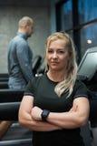 Portrait de femme se tenant avec l'homme s'exerçant sur le tapis roulant Photographie stock libre de droits