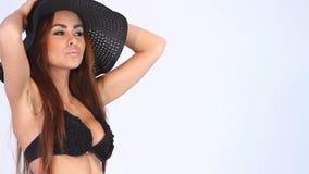 Portrait de femme sexy dans le bikini et le chapeau noirs sur le blanc banque de vidéos