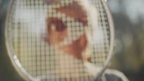 Portrait de femme souriant à la caméra par un plan rapproché de raquette de badminton La femelle est heureuse et sourire clips vidéos