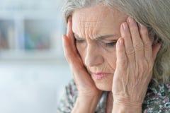Portrait de femme supérieure avec le mal de tête Photographie stock libre de droits