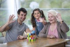 Portrait de femme supérieure avec les mains de ondulation de fils et de petite-fille à la table Photos libres de droits