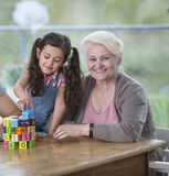 Portrait de femme supérieure de sourire avec la petite-fille jouant avec des blocs d'alphabet à la maison Images stock