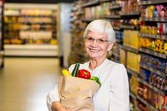 Portrait de femme supérieure de sourire avec le sac d'épicerie Photographie stock