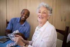 Portrait de femme supérieure jouant des cartes avec l'ami Photos stock