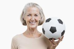 Portrait de femme supérieure tenant le ballon de football sur le fond blanc Image stock