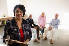 Portrait de femme supérieure tenant le presse-papiers avec des amis s'asseyant à l'arrière-plan Photo stock