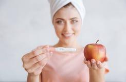 Portrait de femme tenant l'essai et la pomme de grossesse Photo libre de droits