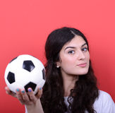 Portrait de femme tenant le football sur le fond rouge Photographie stock libre de droits