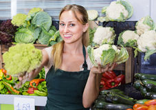 Portrait de femme travaillant dans la boutique de fruit montrant le chou frais Images stock