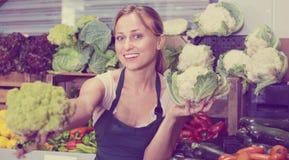 Portrait de femme travaillant dans la boutique de fruit montrant le chou frais Photos stock