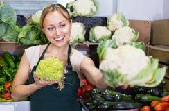 Portrait de femme travaillant dans la boutique de fruit montrant le chou frais Photo stock
