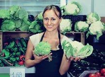 Portrait de femme travaillant dans la boutique de fruit montrant le chou frais Images libres de droits
