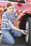 Portrait de femme vérifiant la pression de pneu de voiture utilisant la mesure photos libres de droits