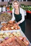 Portrait de femme vendant des légumes dans l'épicerie et le sourire Photos stock