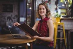 Portrait de fichier de recopie de sourire de jeune femme tout en se reposant au café images stock