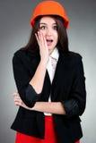 Portrait de fille émotive dans le casque de construction sur le gris Image stock