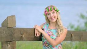 Portrait de fille attirante avec la guirlande de fleur sur sa tête Beau femme avec la guirlande de fleur banque de vidéos