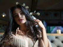 Portrait de fille attirante de brune avec de beaux cheveux se reposant à l'intérieur photos libres de droits