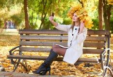 Portrait de fille avec des feuilles sur la tête prenant le selfie en parc de ville d'automne Photographie stock libre de droits
