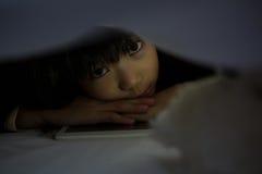 Portrait de fille avec le comprimé au-dessous de la couverture Image libre de droits