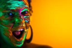 Portrait de fille avec le maquillage fluorescent de peinture Colorant rougeoyant près de la lumière UV Femme avec la bouche ouver image libre de droits