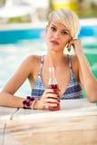 Portrait de fille blonde dans piscine avec la boisson régénératrice Photo stock