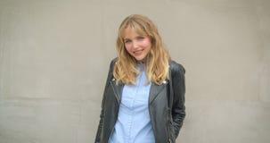 Portrait de fille blonde fraîche dans la veste en cuir posant smilingly dans la caméra sur le fond gris de mur banque de vidéos