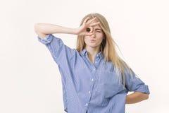 Portrait de fille blonde joyeuse mignonne, regardant la caméra par des doigts dans le geste correct photographie stock libre de droits