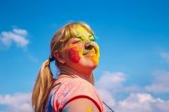 Portrait de fille blonde mignonne avec la peinture colorée sur son visage Image libre de droits