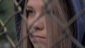 Portrait de fille caucasienne blonde déprimée et triste derrière la barrière de fer Jeune femme derrière la prison de grille de b clips vidéos