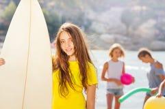 Portrait de fille châtain mignonne avec la planche de surf Photographie stock
