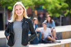 Portrait de fille d'adolescent se tenant hormis des amis dehors Photographie stock