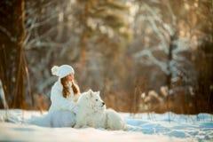 Portrait de fille d'hiver avec le chien de samoyed photographie stock libre de droits