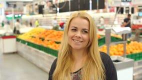 Portrait de fille dans le magasin parmi l'étalage du fruit banque de vidéos