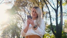 Portrait de fille dans le message blanc d'écriture de chandail sur son smartphone dehors La femme à l'aide de l'instrument numéri clips vidéos