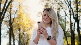 Portrait de fille dans le message blanc d'écriture de chandail sur son smartphone dehors La femme à l'aide de l'instrument numéri banque de vidéos