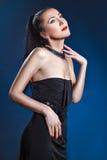 Portrait de fille dans une robe de soirée sur un fond bleu Photographie stock libre de droits
