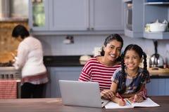Portrait de fille de sourire avec la mère étudiant dans la cuisine Photo stock