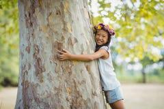 Portrait de fille de sourire étreignant le tronc d'arbre en parc Photo libre de droits