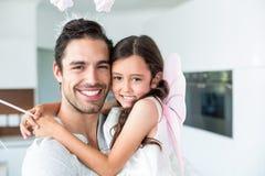 Portrait de fille de transport de père gai dans le costume féerique Images stock