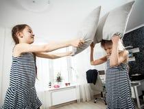 Portrait de fille frappant la soeur avec l'oreiller pendant le combat Images stock