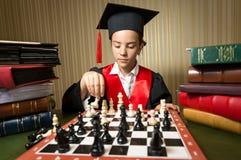 Portrait de fille futée dans le chapeau d'obtention du diplôme jouant des échecs Photo libre de droits